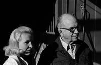 James A. Michener and a woman outside a stable.