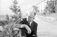 James A. Michener sitting on the ground