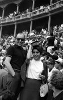 An unidentified man and woman pose in front of a large audience in an outdoor stadium