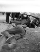 Unidentified men sitting and stretched out on the ground
