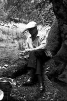 James A. Michener sitting on tree roots