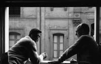 James A. Michener and Robert Daley leaning out a window