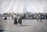 Two women participating in an unknown athletic competition in front of a large crowd, State Normal School campus