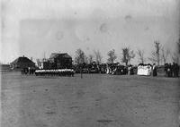 Line of women assembled before crowded bleachers, State Normal School campus