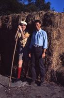 James A. Michener and Robert Vavra lean against bales of hay, ca. 1960s