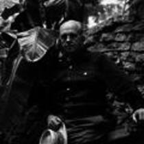 James A. Michener poses in front of a stone wall, ca. unknown