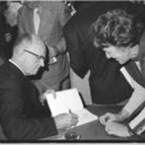 James A. Michener autographs a book during library dedication, 1972
