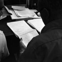 James A. Michener looking at a marked manuscript in Michener Library, ca. 1972