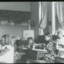 [Children weaving in a classroom]