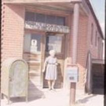 """Mrs. Oram"" at the entrance to the post office in Keota, CO"