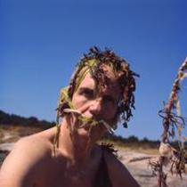 James A. Michener poses with seaweed on his head, 1966