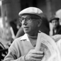 James A. Michener sitting at an outdoor café, holding a newspaper