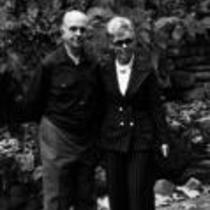 James A. Michener poses with a woman in front of a rock wall, ca. unknown