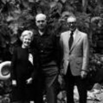 James A. Michener poses with others in front of a rock wall, ca. unknown
