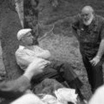 James A. Michener and Kenneth Vanderford conversing with friends in a forest