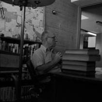 James A. Michener sitting at a desk in a Michener Library office, ca. 1972