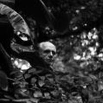 James A. Michener peaks from behind a palm frond, ca. unknown
