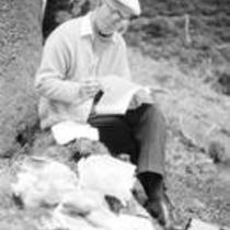 James A. Michener reading on a forest floor