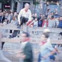 James A. Michener sitting on a fence, as men run inside the fence, ca. 1960s