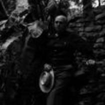 James A. Michener poses in front of a tropically landscaped rock wall, ca. unknown