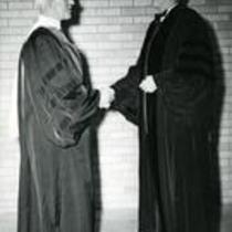 President George Frasier and unidentified man shaking hands