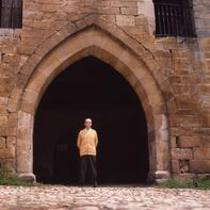 James A. Michener poses in front of a stone archway, ca. 1960s