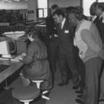 Reference librarian Kathy Earle demonstrates the new online catalog to a group of onlookers at the James A. Michener Library, ca. 1983.
