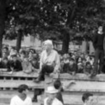 James A. Michener sitting on a fence, as men run inside the fence