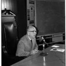 James A. Michener speaks into a microphone, ca. 1972