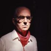 James A. Michener poses against dark backdrop in Pamplona, ca. 1960s
