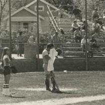 University of Northern Colorado baseball player and bat girl in front of the backstop, 1976