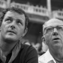 James A. Michener and John Fulton sitting in a stadium