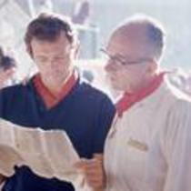 James A. Michener and John Fulton read a newspaper, ca. 1960s.