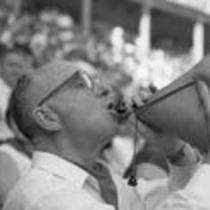 James A. Michener drinking from a water skin