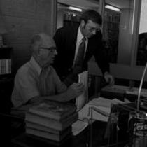 James A. Michener and Dr. J. Gilbert Hause at a desk in an office in Michener Library, ca. 1972