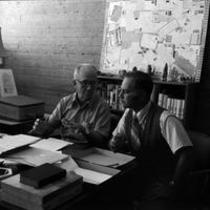 James A. Michener and Thomas C. Harris seated at desk in Michener Library, ca. 1972