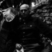 James A. Michener poses in front of a rock wall, ca. unknown