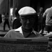 James A. Michener sitting at an outdoor café, reading a newspaper