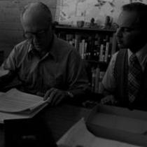 James A. Michener and Thomas C. Harris seated at a desk in Michener Library, ca. 1972