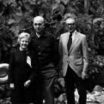 James A. Michener poses with others against a rock wall, ca. unknown