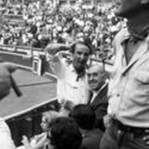 Three men pose for a photograph in the audience of a bullring